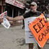 Photo - Doug Phaneuf hands a newspaper to a pedestrian while offering information to passers-by about a rally for Eric Garner, Friday, Aug. 1, 2014, in the Staten Island borough of New York. Garner died after he was put in a chokehold while being arrested last month for selling untaxed loose cigarettes. On Friday, the medical examiner ruled Garner's death to be a homicide caused by a police chokehold. (AP Photo/Julie Jacobson)