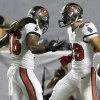 Photo - Tampa Bay Buccaneers wide receiver David Douglas, right, celebrates with wide receiver Chris Denton after scoring a touchdown when he caught a 12-yard pass from Mike Glennon during the second half of a preseason NFL football game against the Miami Dolphins, Saturday, Aug. 24, 2013, in Miami Gardens, Fla. The Buccaneers defeated the Dolphins 17-16. (AP Photo/Wilfredo Lee)