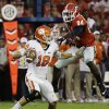 Photo - Clemson quarterback Cole Stoudt, left, scrambles to get away from the defense of Georgia's Leonard Floyd in the second half of an NCAA college football game, Saturday, Aug. 30, 2014, in Athens, Ga. Georgia won 45-21. (AP Photo/David Goldman)