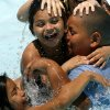 Lily Reyes, 9, bottom, Shawnta Ward, 10, and her brother Raphael Ward, 12, fight over goggles Monday at the Will Rogers Aquatic Center. Photo by Ashley McKee, The Oklahoman