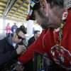 Photo - Sam Hornish Jr. autographs a shirt for David Hales, of La Salle, Ill., right, before the NASCAR Nationwide auto race, Sunday, May 18, 2014, at Iowa Speedway in Newton, Iowa. (AP Photo/Charlie Neibergall)