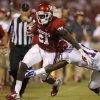 Oklahoma\'s Keith Ford (21) tries to get past Louisiana Tech\'s Lloyd Grogan (11) during a college football game between the University of Oklahoma Sooners (OU) and the Louisiana Tech Bulldogs at Gaylord Family-Oklahoma Memorial Stadium in Norman, Okla., on Saturday, Aug. 30, 2014. Photo by Bryan Terry, The Oklahoman