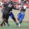 Texas Tech\'s Kerry Hyder (91) grabs Kansas\' Michael Cummings (14) during their NCAA college football game in Lubbock, Texas, Saturday, Nov. 10, 2012. (AP Photo/Lubbock Avalanche-Journal, Zach Long) LOCAL TV OUT
