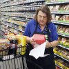 Buy For Less employee Linda Pelletier pulls shopping list items for a customer's Internet order at Uptown Grocery in Edmond. Photo By Paul Hellstern, The Oklahoman