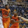 Oklahoma State\'s Marcus Smart, center, grabs a rebound next to teammate Michael Cobbins (20) and West Virginia\'s Aaric Murray, left, and Kevin Noreen (34) during the second half of an NCAA college basketball game in Morgantown, W.Va., on Saturday, Feb. 23, 2013. Oklahoma State defeated West Virginia 73-57. (AP Photo/David Smith) ORG XMIT: WVDS110