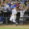 UCLA\'s Eric Filia (4) celebrates after he scored against North Carolina on a two-RBI double by Pat Valaika in the seventh inning of an NCAA College World Series baseball game in Omaha, Neb., Friday, June 21, 2013. UCLA\'s Brian Carroll, left, also scored on the play. (AP Photo/Francis Gardler)