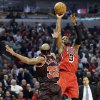 Photo - Miami Heat guard Dwyane Wade (3) shoots over Chicago Bulls guard Richard Hamilton during the first half of an NBA basketball game in Chicago, Thursday, Feb. 21, 2013. (AP Photo/Nam Y. Huh)
