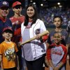 Photo - Plaza Towers Elementary teacher Karen Marinelli is presented with a bat during Friday's Redhawks game against Zephyrs at Chickasaw Bricktown Ballpark.