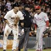 Philadelphia Phillies third baseman Placido Polanco, right, argues a call with umpire Marty Foster, center, as San Francisco Giants\' Buster Posey, left, stands safe at third base during the fifth inning of a baseball game Tuesday, April 17, 2012, in San Francisco. Posey was ruled safe with a steal of third base. (AP Photo/Ben Margot)