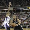 Photo - San Antonio Spurs guard Tony Parker, right, of France, drives to basket against Sacramento Kings guard Isaiah Thomas during the first quarter of an NBA basketball game in Sacramento, Calif., Friday, March 21, 2014.(AP Photo/Rich Pedroncelli)