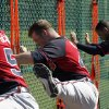 Photo - Atlanta Braves pitcher Craig Kimbrel, center, does leg swings during a spring training baseball workout on Sunday, Feb. 16, 2014, in Kissimmee, Fla. The Braves agreed to terms with Kimbrel on a four-year contract. (AP Photo/Alex Brandon)