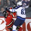 Photo - Winnipeg Jets' Michael Frolik, right, from Czech Republic, collides with Calgary Flames' Mark Giordano during first period NHL action in Calgary, Alberta, Friday, April 11, 2014.  (AP Photo/The Canadian Press, Larry MacDougal)