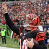 Photo - FILE - In this Dec. 29, 2013 file photo, Cincinnati Bengals quarterback Andy Dalton celebrates after scoring on a 1-yard touchdown run in the second half of an NFL football game  against the Baltimore Ravens, in Cincinnati. Dalton is comparing himself with some of the NFL's top quarterbacks while negotiating a contract extension with the Cincinnati Bengals. He knows the one stat that's holding him back: 0-3 in the postseason.  (AP Photo/Tom Uhlman, File)