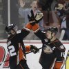 Photo - Anaheim Ducks' Patrick Maroon, left, and Ryan Getzlaf celebrate their team's 5-2 win against the San Jose Sharks after an NHL hockey game on Wednesday, April 9, 2014, in Anaheim, Calif. The Ducks clinched their second straight Pacific Division title. (AP Photo/Jae C. Hong)