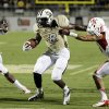 Photo - Central Florida's Storm Johnson (8) tries to get past Houston's Adrian McDonald, right, and Trevor Harris (46) during the first half of an NCAA college football game in Orlando, Fla., Saturday, Nov. 9, 2013. (AP Photo/John Raoux)