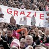 Faithful hold up a banner with pictures of Pope Benedict XVI and writing reading in Italian