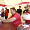 Photo -                    OU fan John Douglas, who is 11 years old and from Tulsa, gets a football signed by OU coach Bob Stoops during Thursday's Sooner Caravan stop in Tulsa.                                                                             Photo by JAMES GIBBARD, Tulsa World