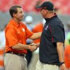 Clemson head coach Dabo Swinney, left, shakes hands with North Carolina State head coach Dave Doeren before an NCAA college football game in Raleigh, N.C., Thursday, Sept. 19, 2013. (AP Photo/Karl B DeBlaker)