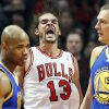 Photo - Chicago Bulls center Joakim Noah, center, reacts after Golden State Warriors' player fouled during the first half of an NBA basketball game in Chicago on Friday, Jan. 25, 2013. (AP Photo/Nam Y. Huh)