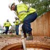 Felix Derousselle guides multiple sections of 10-foot rods into the main sewer line. Edmond city employees assigned to field services , wastewater line management division, use specialty tools to clean out a sewer line behind houses on Rimrock Road on Wednesday. Nov. 16, 2011. The crews use 10 foot rod sections that are coupled and inserted into the main line. Additional sections of rod are added until the obstruction is reached. In this photo, the workers are performing a process called mechanical sawing. Photo by Jim Beckel, The Oklahoman