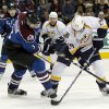 Colorado Avalanche defenseman Ryan O\'Byrne, left, gets tangled up as he blocks a shot off the stick of Nashville Predators right wing Matt Halischuk in the second period of an NHL hockey game in Denver on Saturday, March 30, 2013. (AP Photo/David Zalubowski)