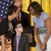 Spencer Hahn, 8, who had a stroke in-utero, looks up at first lady Michelle Obama while on stage with his mother Erica Hahn and The Children\'s Museum of Indianapolis President and CEO Jeffrey Patchen, as they accept a 2014 National Medal for Museum and Library Service during a ceremony in the East Room of the White House, Thursday, May 8, 2014, in Washington. The National Medal is the nation's highest honor given to museums and libraries for service to the community. (AP Photo/Jacquelyn Martin)