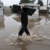Tim Fitzwater, of Geneseo Ill., carries a flat-screen television out of his father\'s mobile home in Geneseo on Thursday, April 18, 2013, after the Geneseo Creek pushed out of its banks by heavy rain, flooded the park and threatened several businesses. (AP Photo/The Dispatch, Todd Mizener) QUAD-CITY TIMES OUT, MANDATORY CREDIT