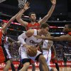 Photo - Los Angeles Clippers' Blake Griffin, center, is defended by Toronto Raptors' Jonas Valanciunas, left, of Lithuania, Kyle Lowry, right, and Andrea Bargnani, of Italy, in the first half of an NBA basketball game in Los Angeles, Sunday, Dec. 9, 2012. (AP Photo/Jae C. Hong)