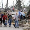 People walk down Magnolia Lane after a tornado touched down in Concord, Ala., outside of Hueytown late Wednesday, April 27, 2011. The damage in the area is extensive with homes and businesses destroyed and people injured. (AP Photo/Birmingham News, Jeff Roberts)