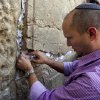 Naftali Bennett, head of the Jewish Home party, places a note in the stones of the Western Wall, the holiest site where Jews can pray, in Jerusalem\'s old city, Monday, Jan. 21, 2013. General elections in Israel will be held Tuesday, Jan. 22, 2013. (AP Photo/Sebastian Scheiner)
