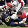 Arizona Cardinals quarterback Kevin Kolb, bottom right, is sacked by St. Louis Rams defensive tackle Jermelle Cudjo, bottom left, as Cardinals\' Adam Snyder gets in on the play during the third quarter of an NFL football game, Thursday, Oct. 4, 2012, in St. Louis. Cudjo was charged with an unnecessary roughness penalty on the play. (AP Photo/Seth Perlman)