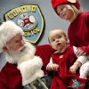 Santa stopped by the Edmond police station Saturday, Dec. 22, 2012, to visit with children, hear their Christmas lists and pose for keepsake photos that were provided for the children by Edmond police department. Sitting on his lap is Clara Dunn, 10 months old. Helping Santa with the children is one of two elves on hand. Playing Santa is Boyd Mize, a retired detective with the Edmond police department. This is the eighth year Mize has donned the Santa suit for the police department\'s day with Santa. But Mize said this is the first year he didn\'t have to wear a fake beard; all the hair on Santa\'s face is natural this year. Photo by Jim Beckel, The Oklahoman