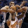 Photo - San Antonio Spurs' Tim Duncan pulls the ball away from Phoenix Suns' P.J. Tucker (17) during the second half of an NBA basketball game, Wednesday, Dec. 18, 2013, in Phoenix. The Spurs won 108-101. (AP Photo/Matt York)