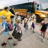 Music teacher Amy Thomas greets students arriving by bus as a thunderstorm moves through on the first day of school at Rose Union Elementary in the Deer Creek School District in Oklahoma City Thursday, Aug. 11, 2011. Photo by Paul B. Southerland, The Oklahoman ORG XMIT: KOD