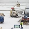 A plane is deiced on a snowy Presidents Day at Washington\'s Ronald Reagan National Airport Monday, Feb. 15, 2016. The bitter cold was replaced by snow, sleet and rain Monday in the mid-Atlantic states and the South, but many residents were able to hunker down at home with federal offices and many businesses closed for Washington\'s Birthday. (AP Photo/Andrew Harnik)
