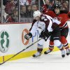 Photo - Colorado Avalanche's Tyson Barrie controls the puck as he is checked by New Jersey Devils' Ryan Clowe, right, during the second period of an NHL hockey game Monday, Feb. 3, 2014, in Newark, N.J. (AP Photo/Bill Kostroun)