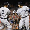 New York Yankees\' Derek Jeter, left, high-fives teammate Alex Rodriguez after scoring a run on a double by Ichiro Suzuki, of Japan, in the first inning of Game 1 of the American League division baseball series against the Baltimore Orioles on Sunday, Oct. 7, 2012, in Baltimore. (AP Photo/Nick Wass)