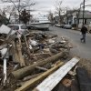 A cleanup crew walks past piles of debris and a beached motorboat in the middle of a road in the oceanside community of Port Channel, New York, Thursday, Nov. 1, 2012. Sandy, the storm that made landfall Monday, caused multiple fatalities, halted mass transit and cut power to more than 6 million homes and businesses. (AP Photo/Mark Lennihan) ORG XMIT: NYML137