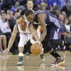 Photo - Charlotte Bobcats' Kemba Walker (15) battles for a loose ball against Golden State Warriors' Stephen Curry (30) during the first half of an NBA basketball game in Oakland, Calif., Tuesday, Feb. 4, 2014. (AP Photo/Tony Avelar)