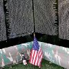 Photo -  A bottle of beer left near a flag at The Moving Wall exhibit, a replica of Vietnam Veterans Memorial in Washington DC, at  Woodland Park in Shawnee , Okla., on Sunday, August 23, 2009. By John Clanton, The Oklahoman ORG XMIT: KOD