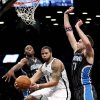 Photo -   Brooklyn Nets' Deron Williams, center, passes the ball around Orlando Magic's Josh McRoberts, right, and Moe Harkless during the first half of an NBA basketball game in New York, Sunday, Nov. 11, 2012. (AP Photo/Seth Wenig)