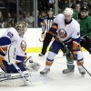 New York Islanders goalie Kevin Poulin (60) stops a shot as defenseman Calvin de Haan (44) and Dallas Stars center Vernon Fiddler (38) watch in the first period of an NHL hockey game, Sunday, Jan. 12, 2014, in Dallas. (AP Photo/Tony Gutierrez)