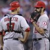 Photo - Los Angeles Angels catcher Chris Iannetta and pitcher Matt Shoemaker confer after Philadelphia Phillies' Chase Utley hit a triple in the fourth inning of a baseball game, Tuesday, May 13, 2014, in Philadelphia. (AP Photo/Laurence Kesterson)