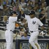 Photo - New York Yankees' Zoilo Almonte, right, celebrates with third base coach Rob Thomson as he heads to home plate after hitting a home run during the sixth inning of a baseball game on Friday, June 21, 2013, in New York. (AP Photo/Frank Franklin II)