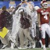 Texas A&M head coach Kevin Sumlin is dunked on the sideline in the final seconds of the Cotton Bowl NCAA college football game against Oklahoma Friday, Jan. 4, 2013, in Irving, Texas. Texas A&M won 41-13. (AP Photo/LM Otero)