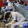 Photo - Los Angeles Dodgers' Dan Haren sits dejectedly in the dugout after giving up a 2-run home run to Arizona Diamondbacks' Eric Chavez after Haren pitched in the fifth inning of a baseball game on Sunday, May 18, 2014, in Phoenix. (AP Photo/Ross D. Franklin)