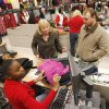 Photo - Cashier Precious Turner rings up the purchases for customers Adam and Christy Tester during early morning Black Friday shopping at the Kohl's store in Midwest City, OK, Friday, November 23, 2012, By Paul Hellstern, The Oklahoman