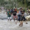 Residents cross a river in the flash flood-hit village of Andap, New Bataan township, Compostela Valley in southern Philippines Wednesday, Dec. 5, 2012. Typhoon Bopha, one of the strongest typhoons to hit the Philippines this year, barreled across the country\'s south on Tuesday, killing scores of people while triggering landslides, flooding and cutting off power in two entire provinces. (AP Photo/Bullit Marquez)