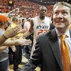 Photo - OSU coach Travis Ford, front, smiles at fans as he and James Anderson leave the court following the Cowboys' 85-77 upset of top-ranked Kansas on Saturday. Photo by  Nate Billings,  The Oklahoman