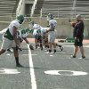 Photo - In this photo taken on Aug. 15, 2014, Eastern Michigan players line up for a play during NCAA college football practice at Rynearson Stadium in Ypsilanti, Mich.. The school has replaced the stadium's green artificial turf with gray FieldTurf. (AP Photo/Mike Householder)